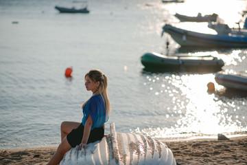 Stylish girl sitting on the beach on a beautiful sunset background