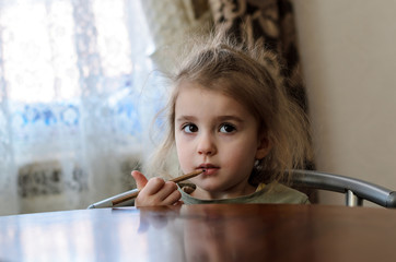 a little girl in a khaki shirt with wide open brown eyes sits at a brown wooden table and pencil outlines her lips