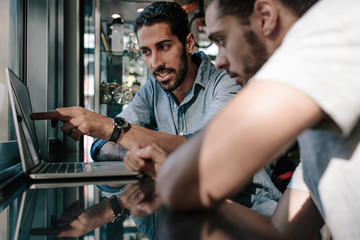 Sports shop owner discussing ideas with colleague using computer