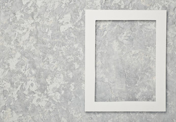Empty white frame on a gray concrete wall. Copy space..
