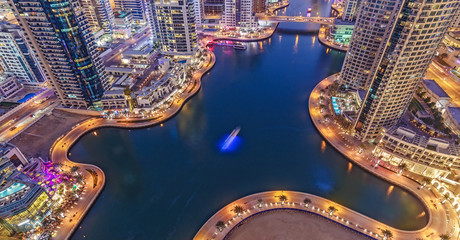 Spectacular view of a big modern city at night. Dubai Marina creek with skyscrapers. Scenic nighttime skyline.