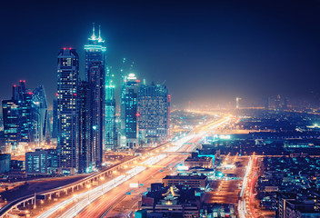 Spectacular nighttime skyline of a big modern city at night.. Dubai, UAE. Aerial view on highways and skyscrapers.
