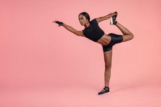 African woman practicing Natarajasana yoga pose