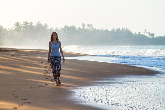 The girl is walking along the beach. Bentota, Sri Lanka