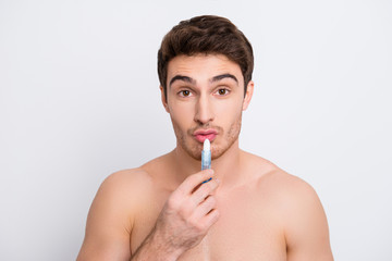 Cream lotion people person concept. Close up portrait of handsome attractive cute lovely tender gentle guy applying balm on cracked dry lips using hygienic balm isolated on gray background