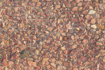 masonry of the old wall of rough cut red stone