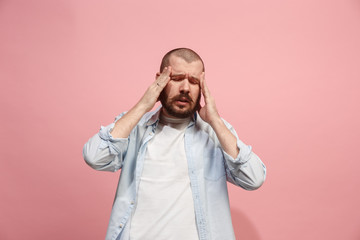 Man having headache. Isolated over pink background.