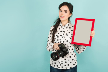 Young woman with camera and frame