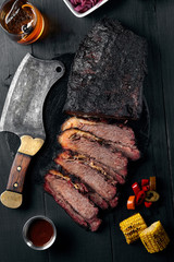 Fresh Brisket BBQ beef sliced for serving against a dark background with sauce, hot peppers and corn.