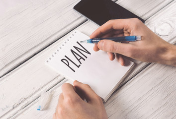 man writes a plan