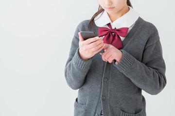 携帯電話を見る制服を着た女の子