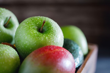 Wet fresh green fruit and vegetables in a wooden box in a kitchen. The concept of organic and healthy food.
