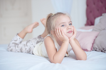 Cute little blond girl lying on a bed looking up into the air with a happy expression as she watches something.