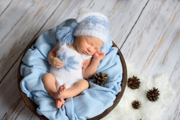 sweet newborn baby sleeps in a knitted hat in a basket on a blue blanket on a blue wooden background.