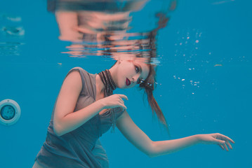 surreal art portrait of young woman in grey dress and beaded scarf underwater in the swimming pool