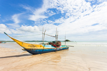 Weligama Beach, Sri Lanka - A traditional fishing boat at the sandy beach of Weligama