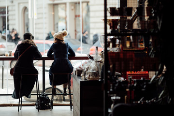 Two woman sit on the table at coffee place and talk to each other