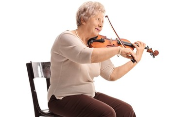 Elderly woman seated on a chair playing a violin