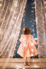 Cute child girl stay near the window and looking at the stars. Little kid stay at windowsill around garlands. Child like in fairytale. Curly child enchanted stars and sky.