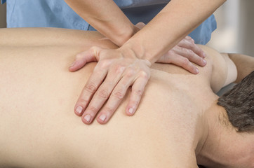 Physiotherapist, chiropractor giving a back massage to man patient. Osteopathy