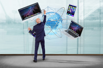 Businessman in front of a wall with a Computer and devices displayed on a futuristic interface with international network  - 3d render