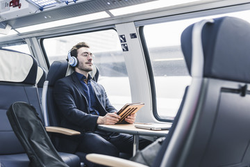 Businessman in train relaxing listening to music