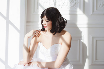 Portrait of young attractive brunette with short hair in a wedding dress. Standing at the white walls. Joyful bride.