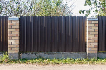 fence of the profiled metal. poles made of decorative yellow brick
