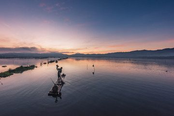 Fisherman works on bamboo raft in early morning