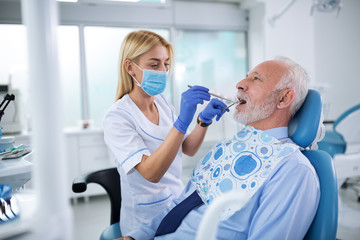 Young dentist examining  teeth of an elderly patient