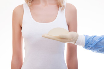 Silicone breast implant on hands. Doctor tries on silicone breasts