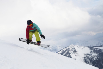 The girl on snowboard jumps in the cloudy mountains