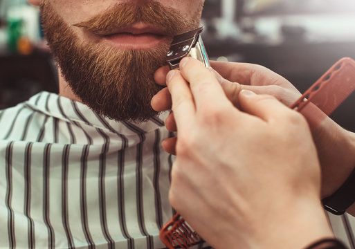 Details of trimming. Cropped closeup of a barber trimming beard to his client