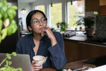 Thoughtful businesswoman holding cup while sitting with laptop on table in home office