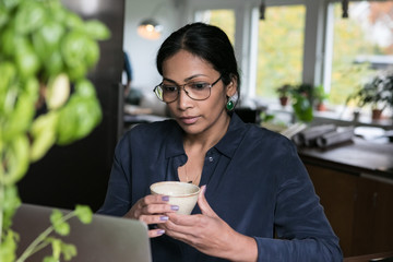 Businesswoman holding cup while looking at laptop in home office