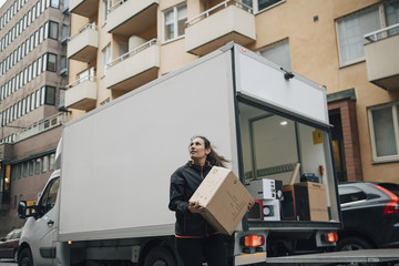 Woman carrying box while standing by delivery van in city
