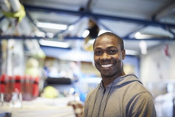 Portrait of smiling mid adult male volunteer standing in illuminated warehouse