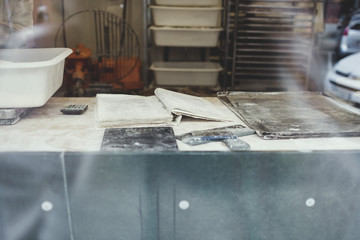 Book on messy table seen through glass at bakery
