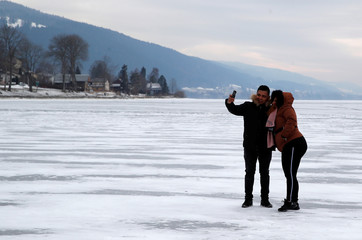 People take a selfie on the ice of the frozen Lake of Joux in Le Pont