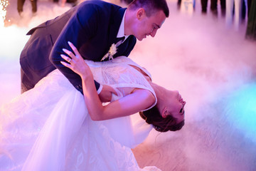 Groom whirls bride while they dance in a smoke for the first time