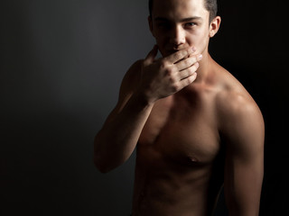 Handsome athletic guy with a naked torso on a black background