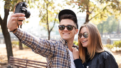 Man and young woman shoots self portrait on on old film camera