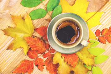 Coffee cup and autumn leaves over wood background.