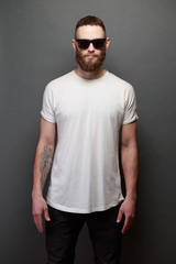 Hipster handsome male model with beard wearing white blank t-shirt with space for your logo or