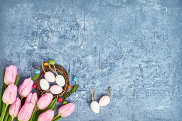Easter wreath, pink tulips and decorative Easter eggs on blue background. Top view, copy space