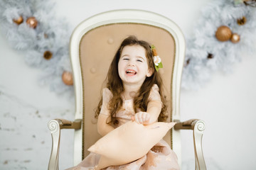 Charming little girl looks like a princess sitting on the chair in a cosy white room