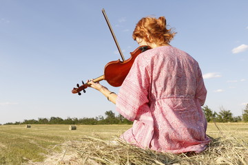 Young violinist seating on the sheaf in the wheat field and playing violin