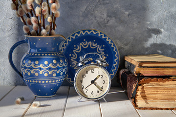 Springtime background with alarm clock, ceramic plate and a pitcher with pussy-willow and old books on wood