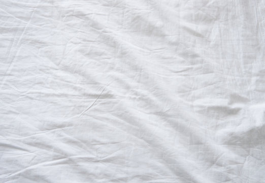 Top view of wrinkles on an unmade bed sheet after waking up in the morning.