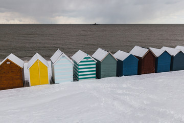 Row of beach huts in winter snow on coast of Herne Bay, Kent, England